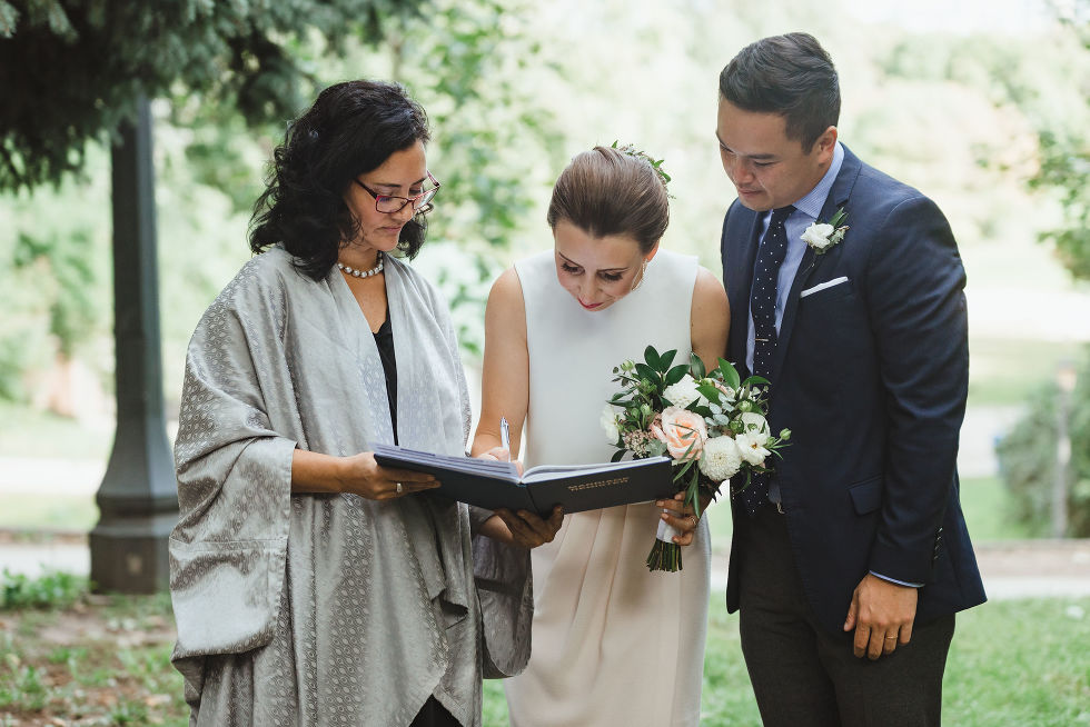bride signing wedding certificate as groom and officiant look on Trinity Bellwoods Park Toronto