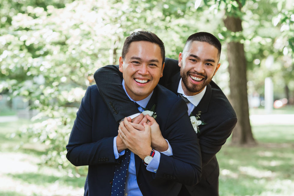 groomsman with his arms swung around the groom as they smile Trinity Bellwoods Park wedding ceremony Toronto