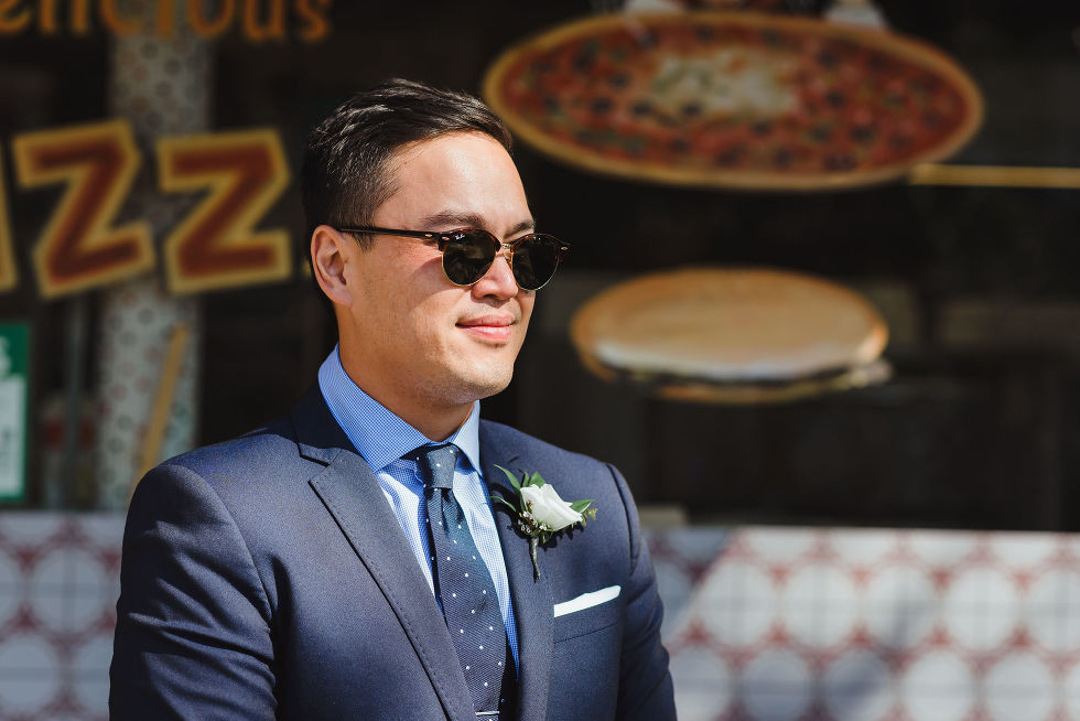 grooms in a blue suit and polkadot tie with white boutonniere standing in front of Bitondo