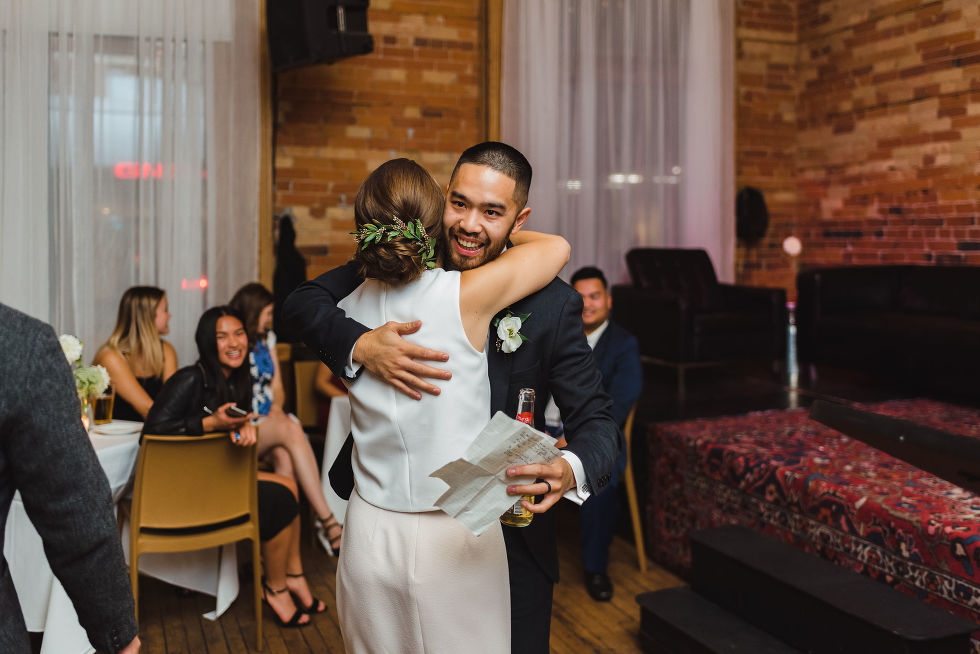 groomsman hugging the bride holding a beer and piece of paper during the wedding reception at the Gladstone Hotel in Toronto