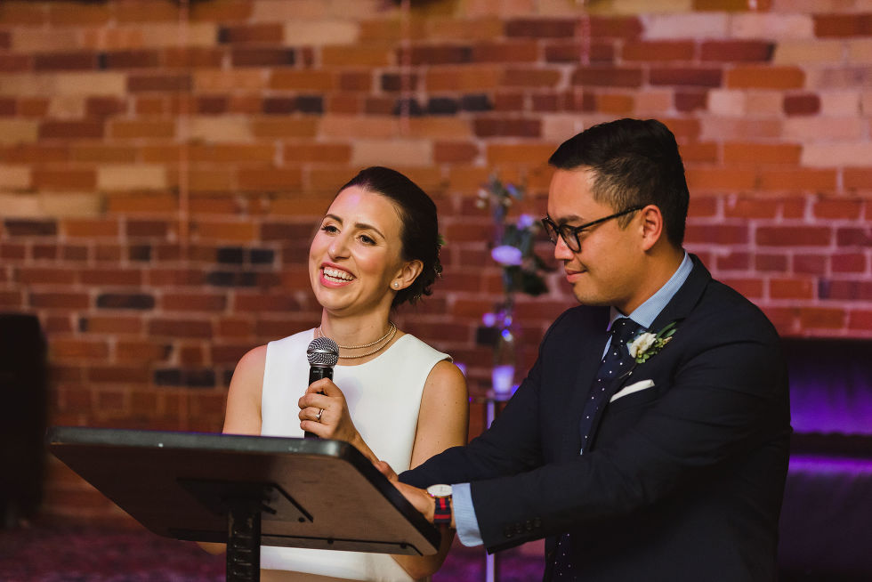 bride smiling as she and the groom give their speech from the podium at the Gladstone Hotel in Toronto