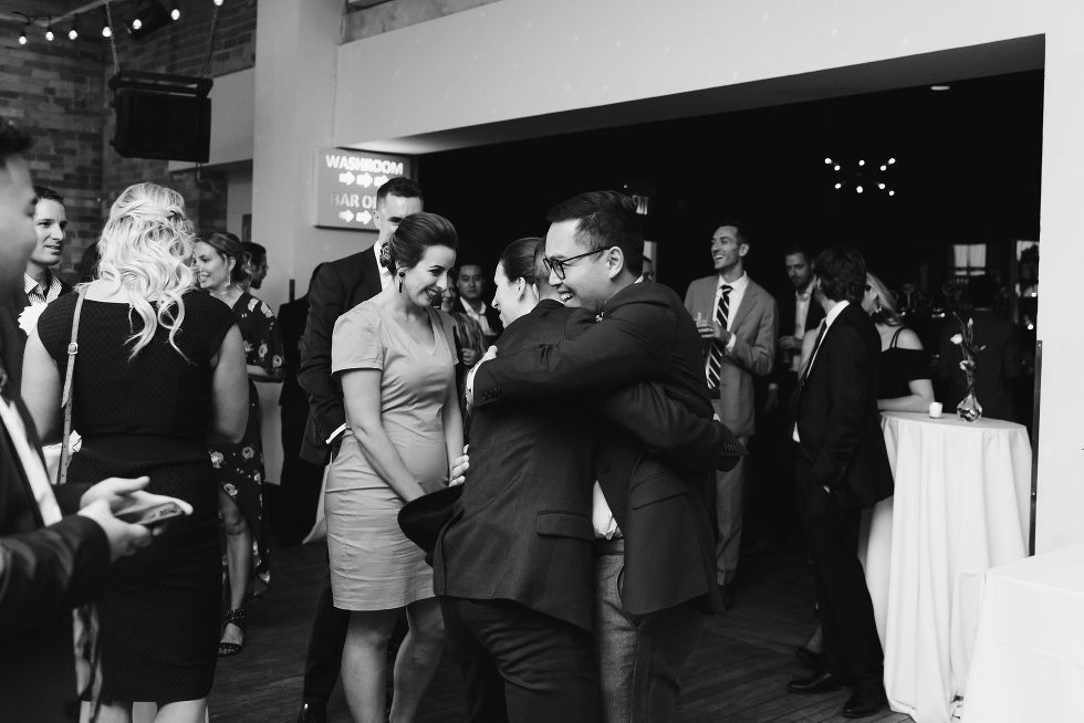 groom hugging a wedding guest during the reception at the Gladstone Hotel in Toronto