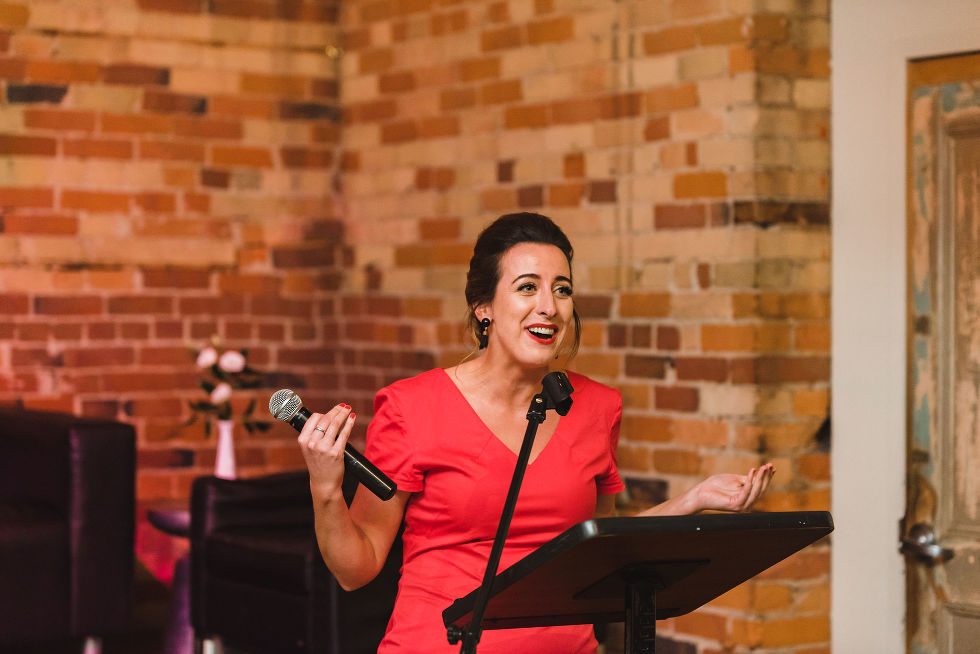 woman in a red dress giving a wedding speech at the Gladstone Hotel in Toronto how to best plan your wonderful wedding your way