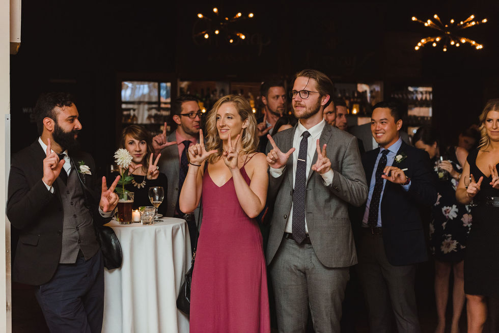 wedding guests all doing hand symbols during a wedding speech at the Gladstone Hotel in Toronto