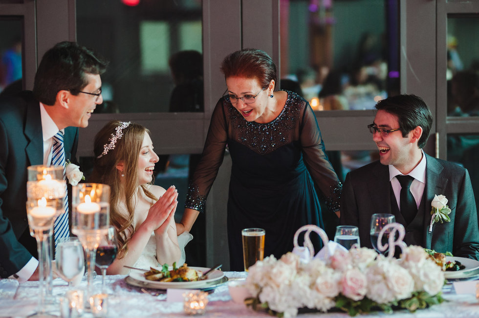 mother and father of the groom speaking to the bride and groom at the head table Steam Whistle Brewing wedding photography