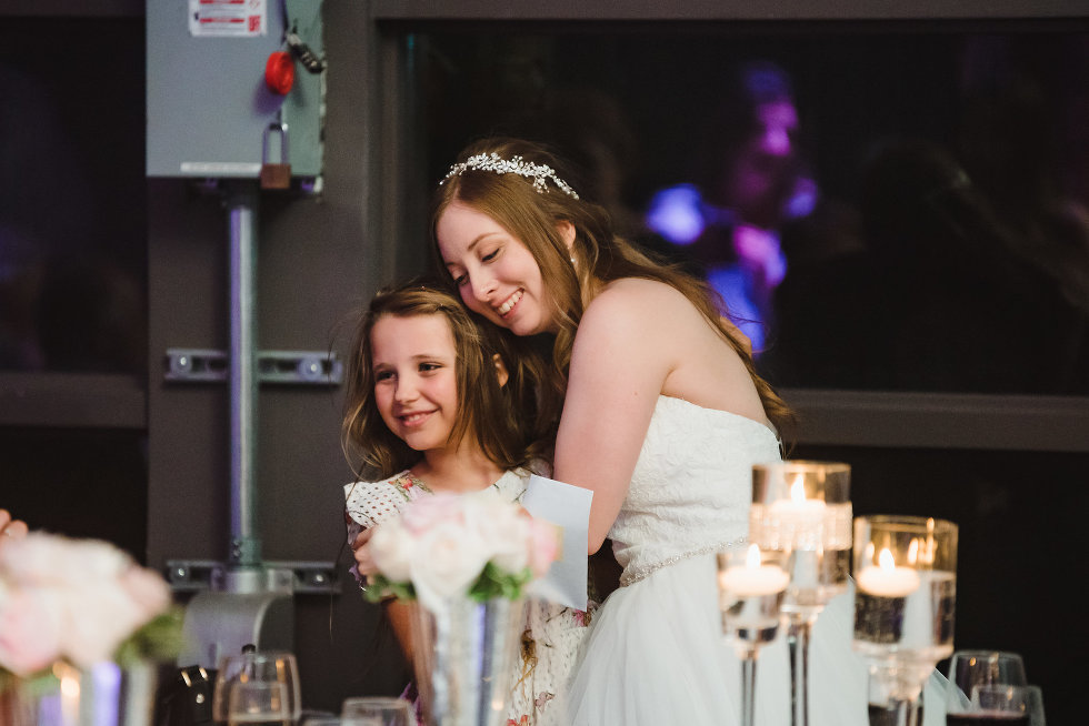 bride hugging a child at her wedding inside Steam Whistle Brewing Toronto Canada