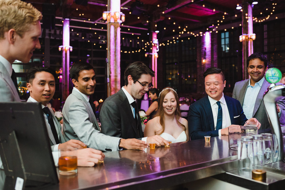 bride and groom about to take a shot with wedding guests at the bar inside Steam Whistle Brewing Toronto wedding photography Gillian Foster