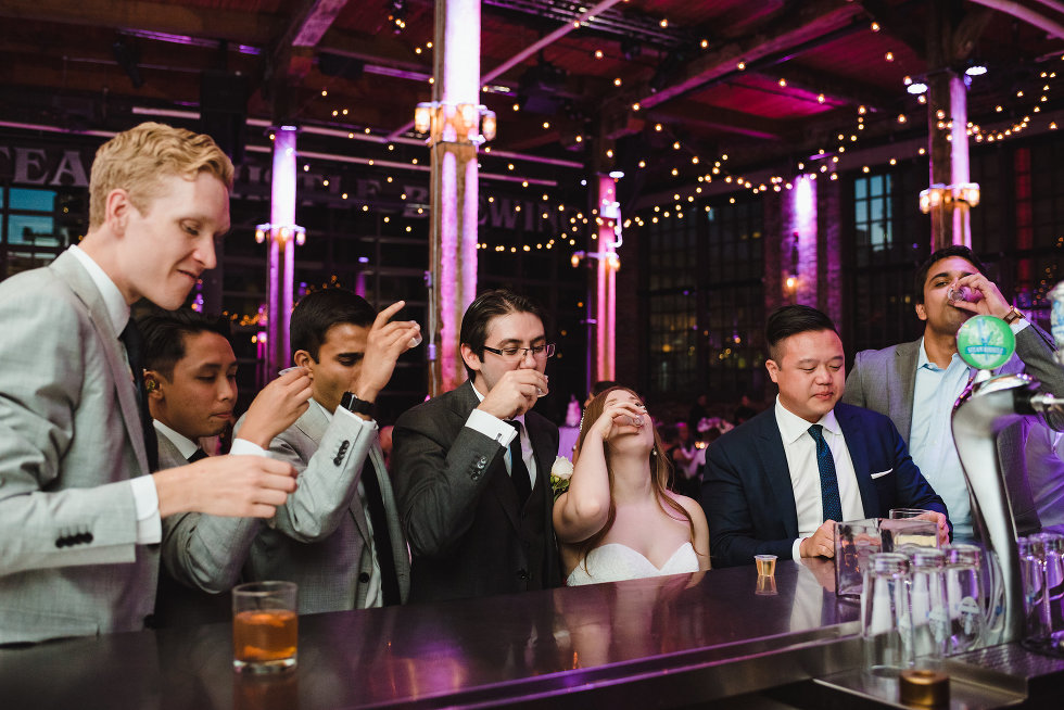bride and groom taking a shot with wedding guests at the bar inside Steam Whistle Brewing Toronto wedding photography Gillian Foster