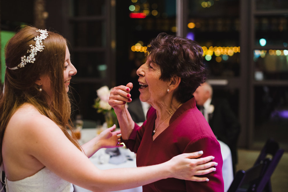 bride smiling at talking with wedding guest during her wedding at Steam Whistle Brewing