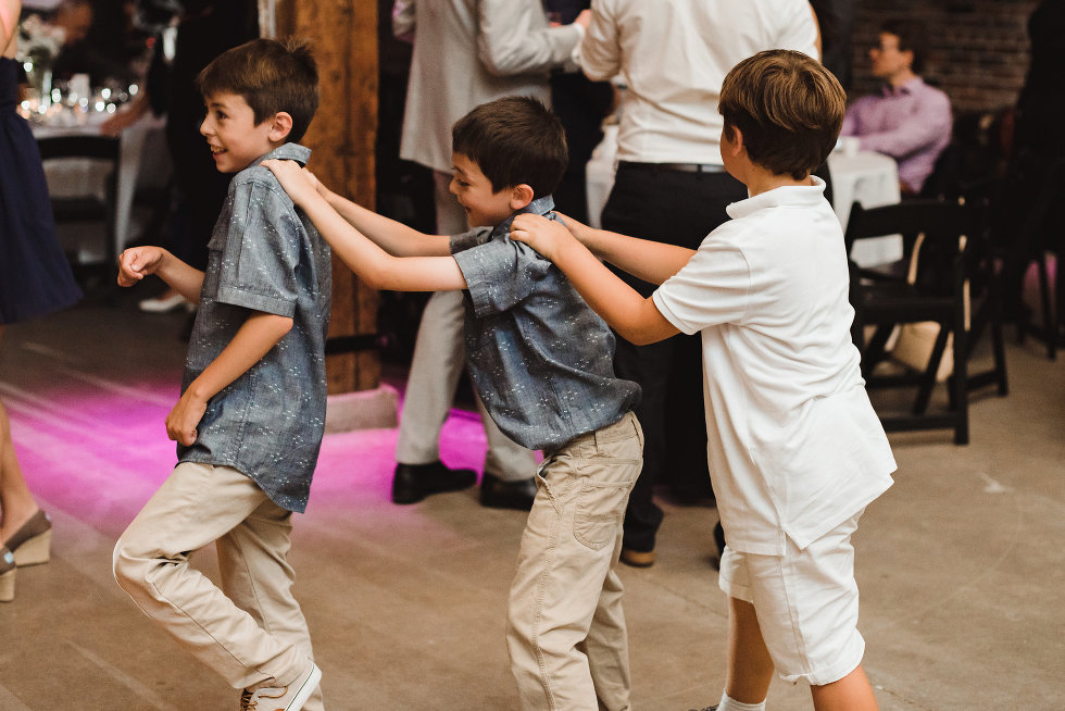 three little boys forming a conga line during a wedding at Steam Whistle Brewing