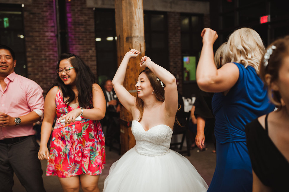 bride with her arms up and dancing during wedding reception at Steam Whistle Brewing Toronto wedding photographer Gillian Foster