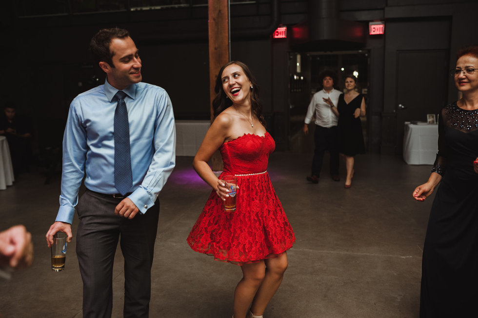couple of wedding guests dancing and holding pints of beer at Steam Whistle Brewing