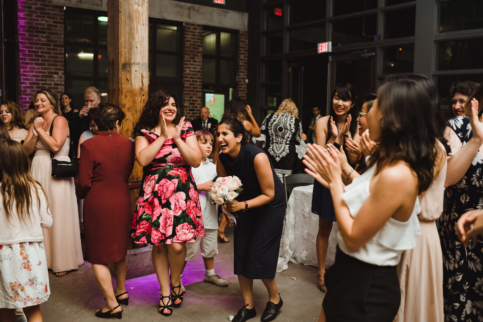 woman laughing as she caught the wedding bouquet as other wedding guests clap around her Steam Whistle Brewing Toronto wedding photography