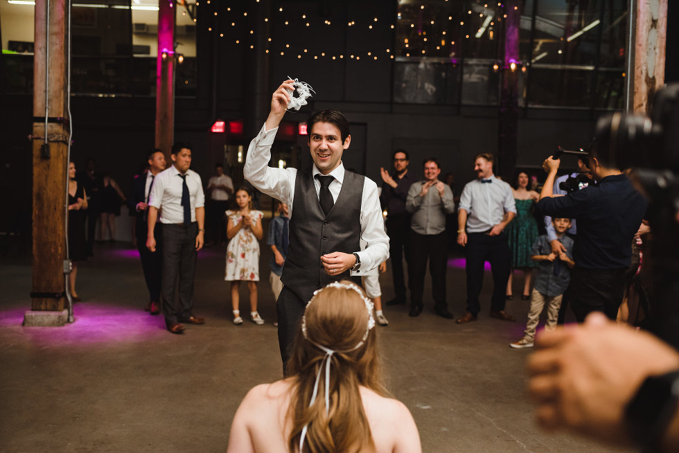 groom about to toss the garter to a group of wedding guests behind him Steam Whistle Brewing