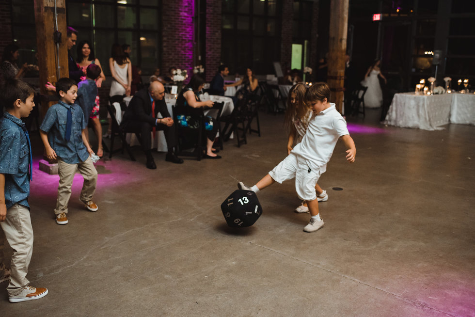 a group of children kicking around an oversized dice during a wedding at Steam Whistle Brewing