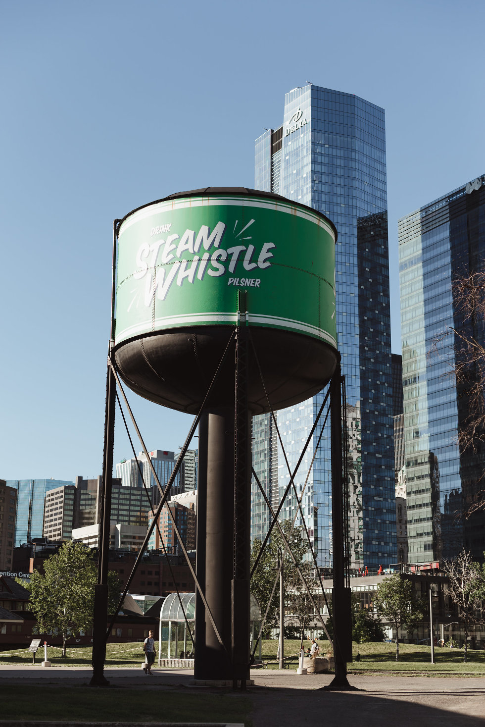 green and white Steam Whistle Brewing water tower in front of Toronto skyline