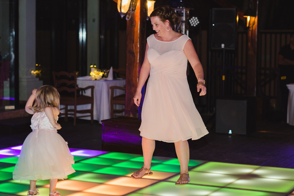 wedding guest and her little girl dancing on multi-coloured light up dance floor during wedding reception at Now Sapphire Resort in Mexico