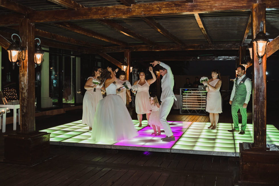 brides and wedding guests dancing on multi-coloured light up dance floor during wedding reception at Now Sapphire Resort in Mexico