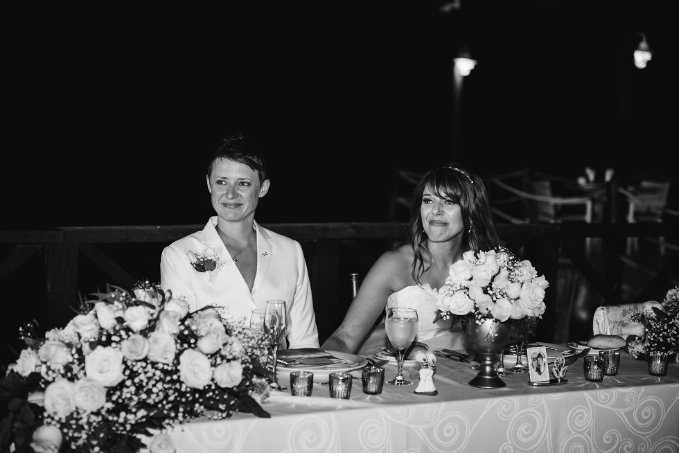 brides smiling and teary while sitting at head table and listening to speeches during wedding reception at Now Sapphire Resort in Mexico
