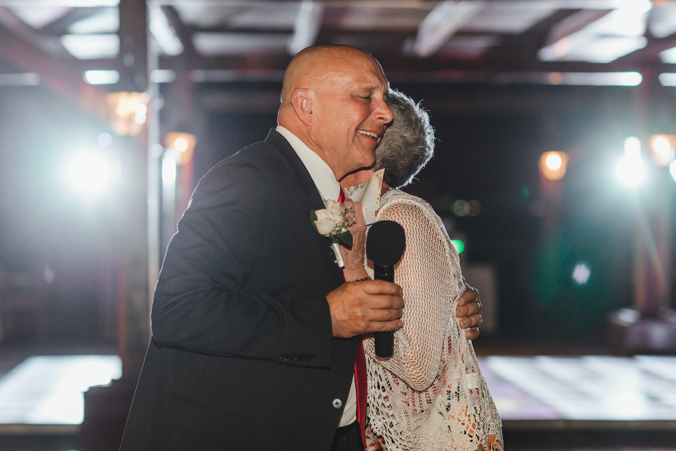 parents of the bride hug while giving wedding speech at Now Sapphire Resort in Mexico