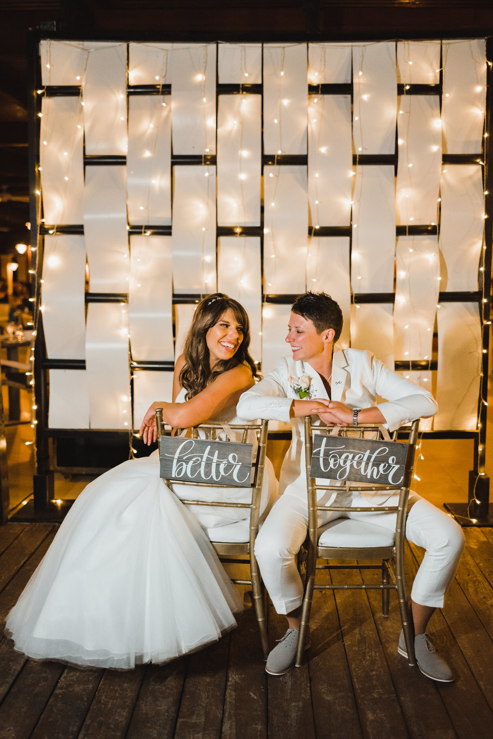 "brides posing on chairs that read ""better together"" during wedding reception at Now Sapphire Resort in Mexico"