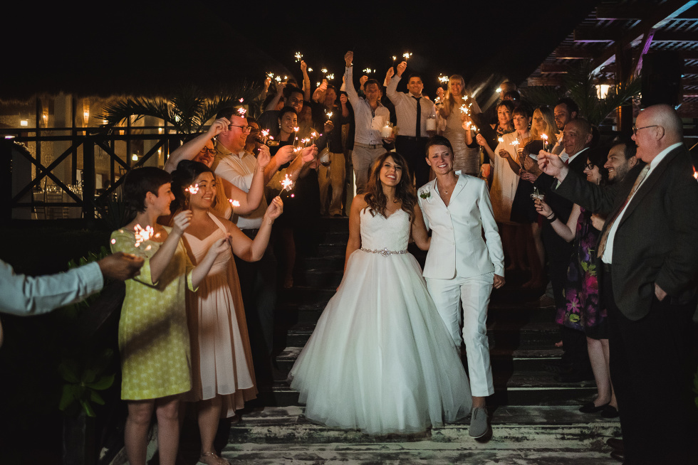 brides exiting wedding reception with wedding guests surrounding them and holding sparklers at Now Sapphire Resort in Mexico