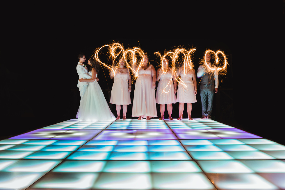 brides slow dancing on multi-coloured light up dance floor next to wedding party using sparklers to draw hearts in the air Now Sapphire Resort Mexico