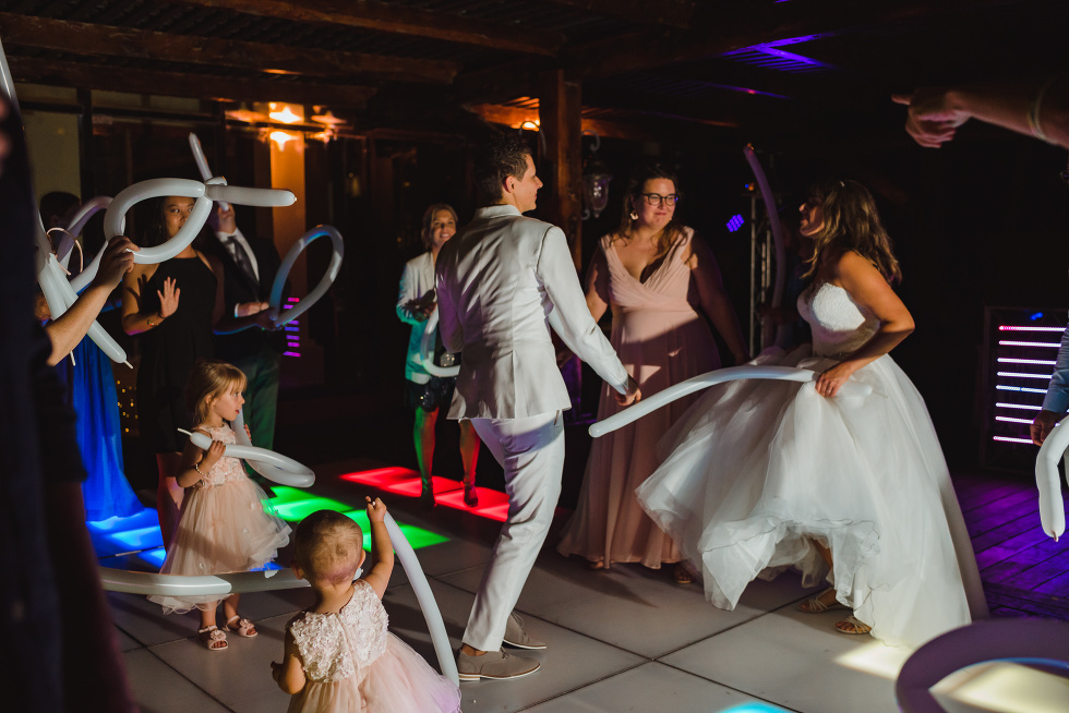 brides and their wedding guests partying with ballon animals on multi-coloured light up dance floor wedding reception at Now Sapphire Resort in Mexico