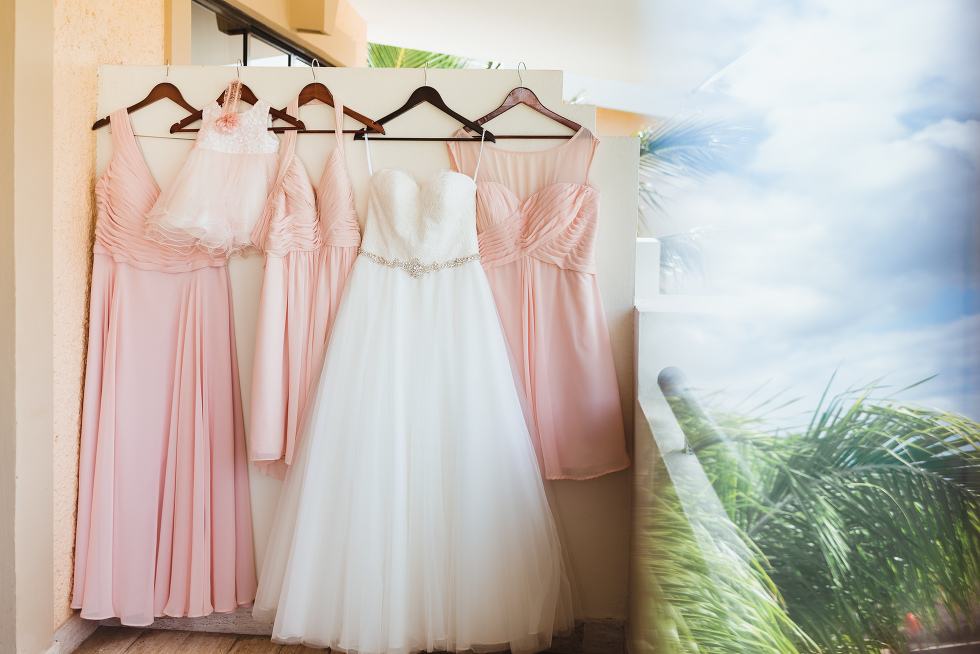 white brides dress and pink bridesmaids dresses hung on hangers before destination wedding at Now Sapphire Resort in Mexico