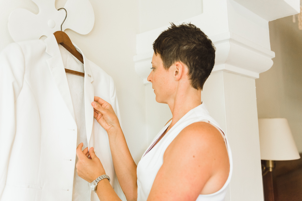bride checking the lapels of her white wedding jacket before destination wedding at Now Sapphire Resort in Mexico