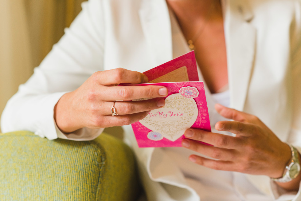 "bride reading a card that says ""for my bride"" on the front before destination wedding at Now Sapphire Resort in Mexico"