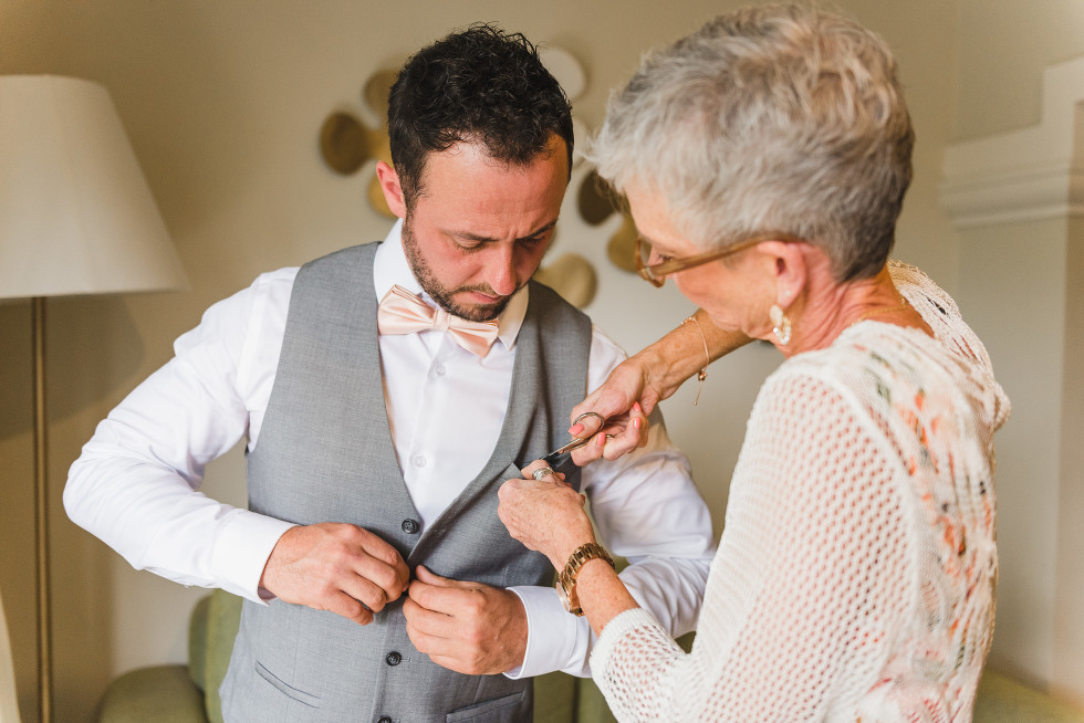woman with scissors making alterations to a mans vest before wedding at Now Sapphire Resort in Mexico
