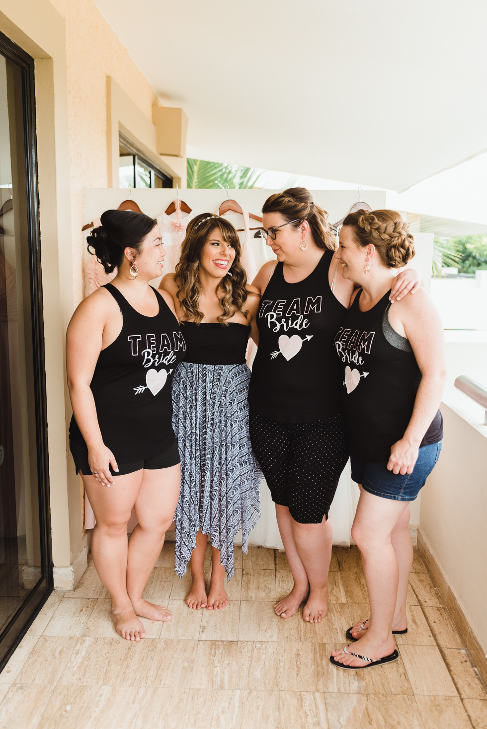 "bride surrounded by bridesmaids wearing ""Team Bride"" black tank tops before destination wedding at Now Sapphire Resort in Mexico"