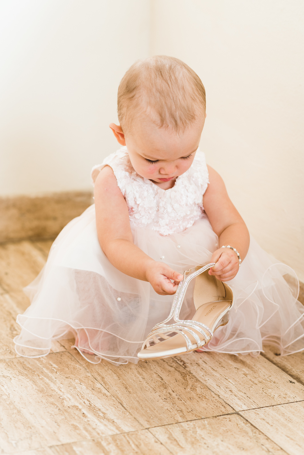 baby in a dress examining brides wedding shoe before ceremony at Now Sapphire Resort in Mexico