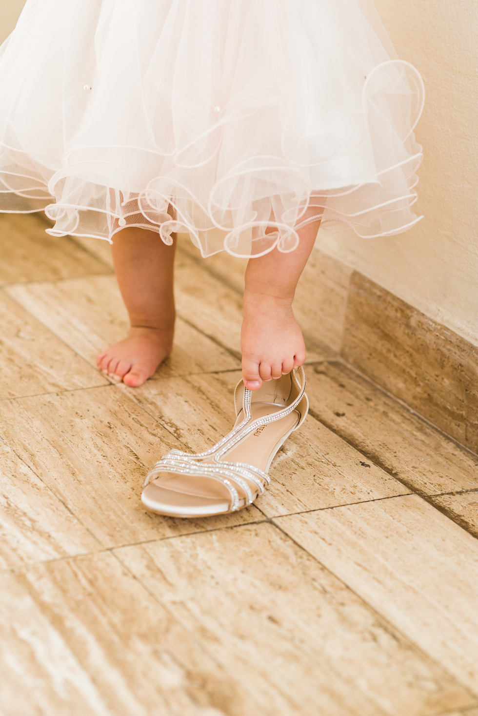 baby in a dress trying to get her foot into brides wedding shoe before ceremony at Now Sapphire Resort in Mexico
