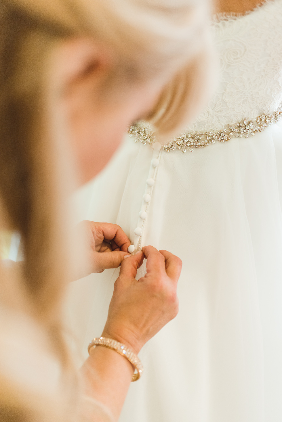 woman doing up buttons of brides white wedding dress ahead of ceremony at Now Sapphire Resort in Mexico