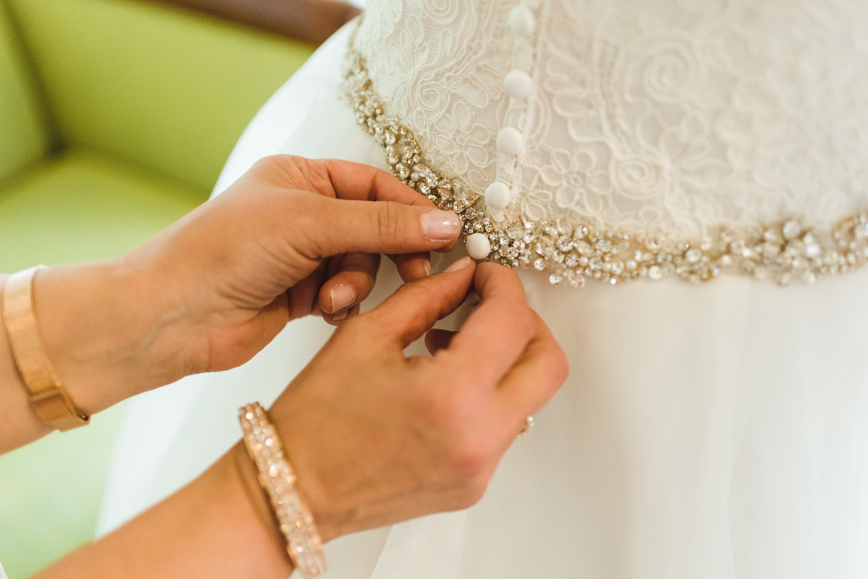 woman doing up buttons of brides white wedding dress covered with jewels ahead of ceremony at Now Sapphire Resort in Mexico