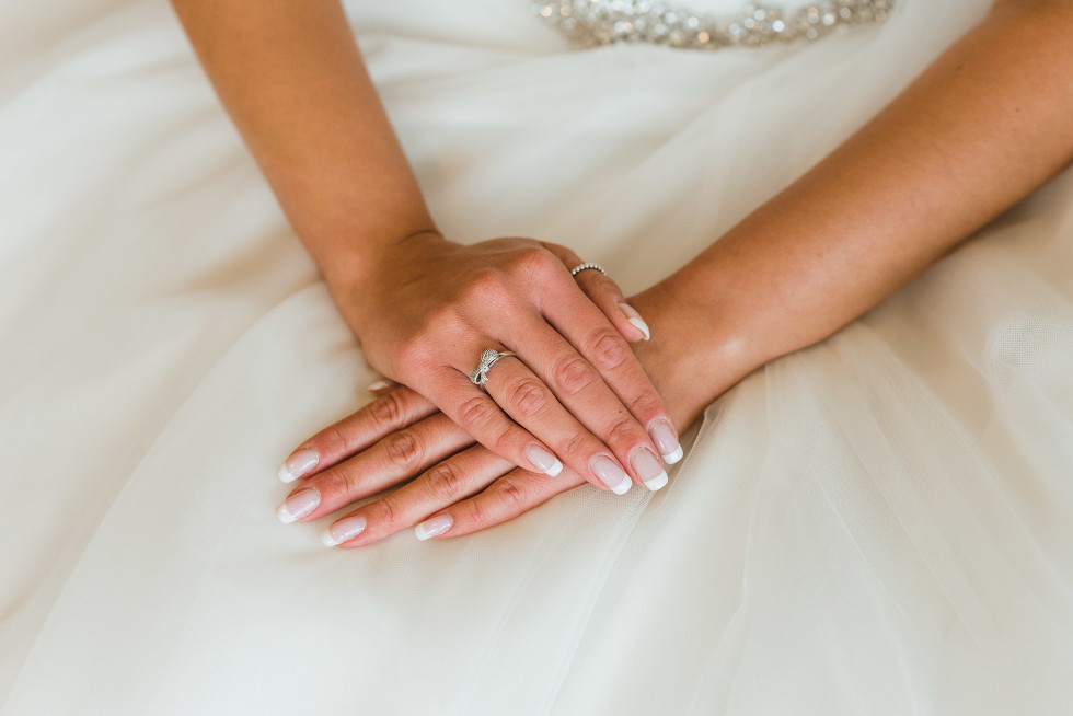bride with her hands crossed over each other on her white wedding dress before wedding at Now Sapphire Resort in Mexico