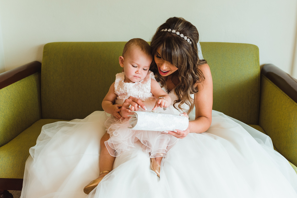 bride sitting in a green chair in her white wedding dress with a baby showing her her white purse before wedding ceremony at Now Sapphire Resort in Mexico