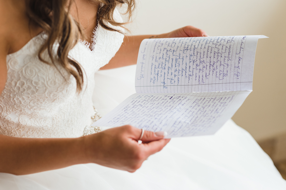 bride in her white wedding dress sitting down reading a letter before wedding ceremony at Now Sapphire Resort in Mexico