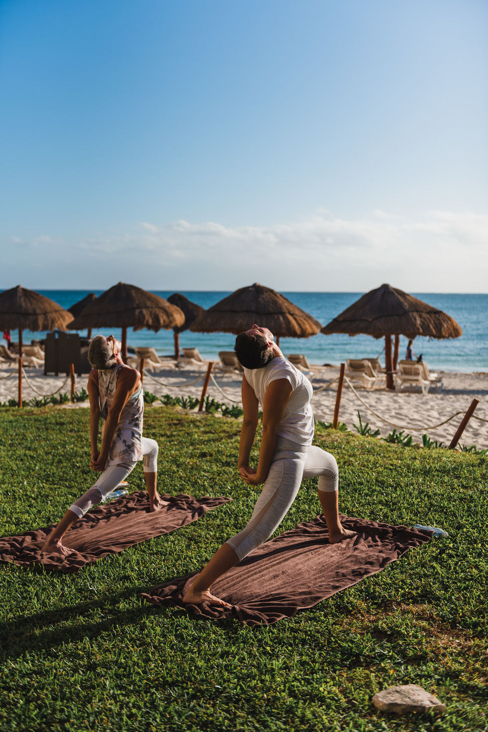 wedding party doing morning yoga on the beach at Now Sapphire Resort in Mexico