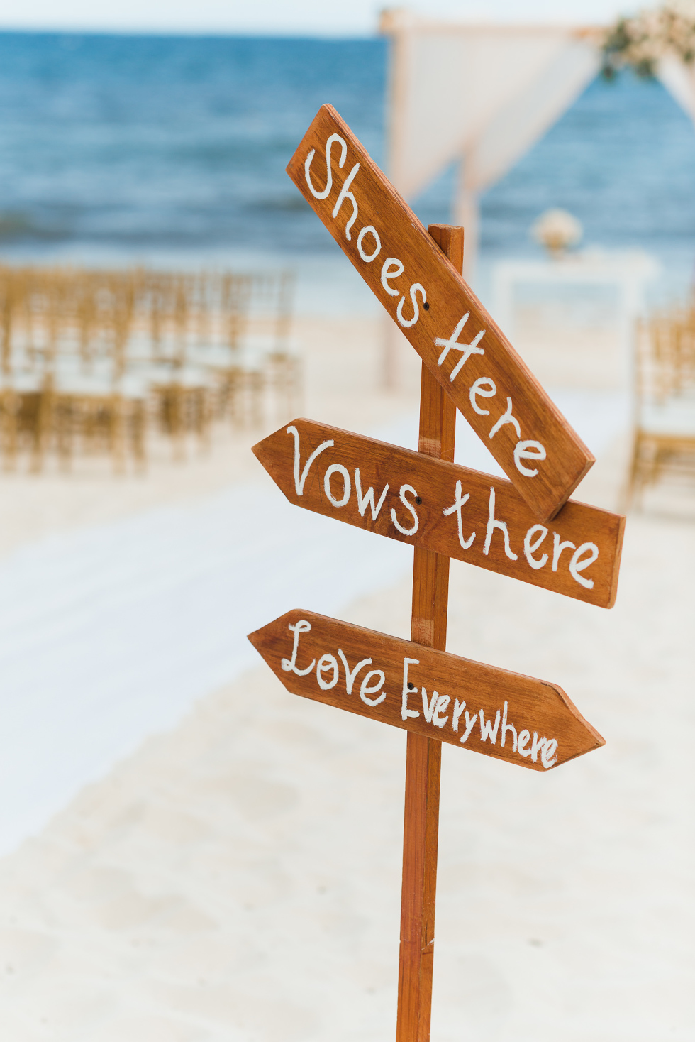 "sign with arrows reading ""shoes here, vows there, love everywhere"" at the entrance of beach destination wedding at Now Sapphire Resort in Mexico"