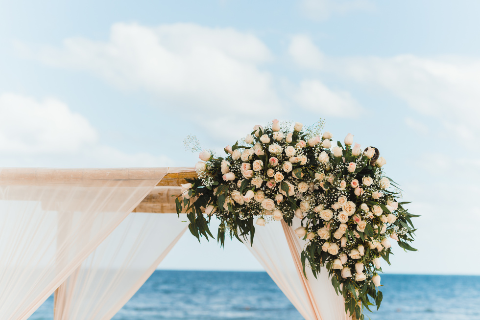 pink floral bouquet on top of wedding alter set up on beach in front of the ocean at the Now Sapphire Resort in Mexico how to be really relaxed during your wedding
