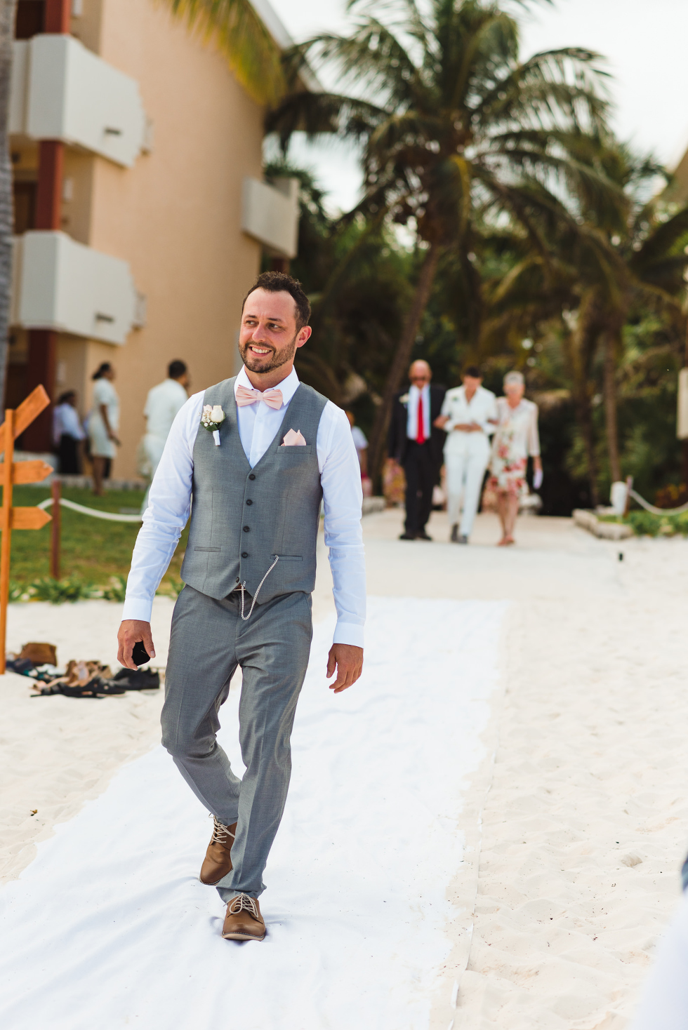 man in grey vest suit and pink bowtie walking into beach wedding ceremony at Now Sapphire Resort in Mexico