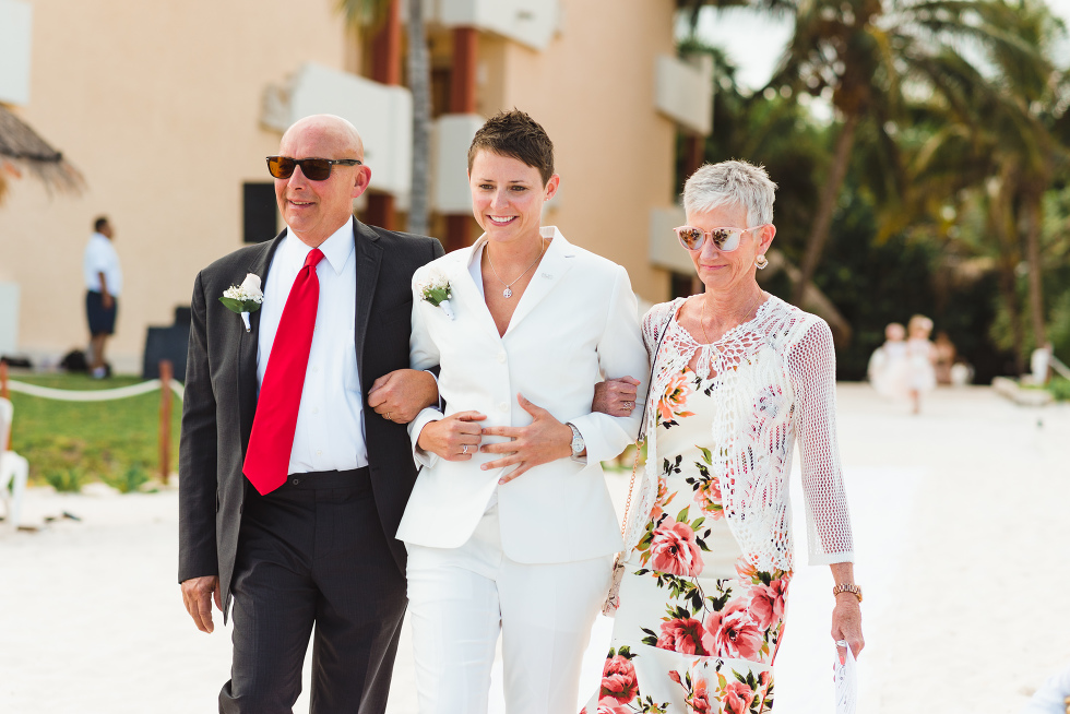 bride being walked down the aisle by her mother and father during beach ceremony at Now Sapphire Resort in Mexico
