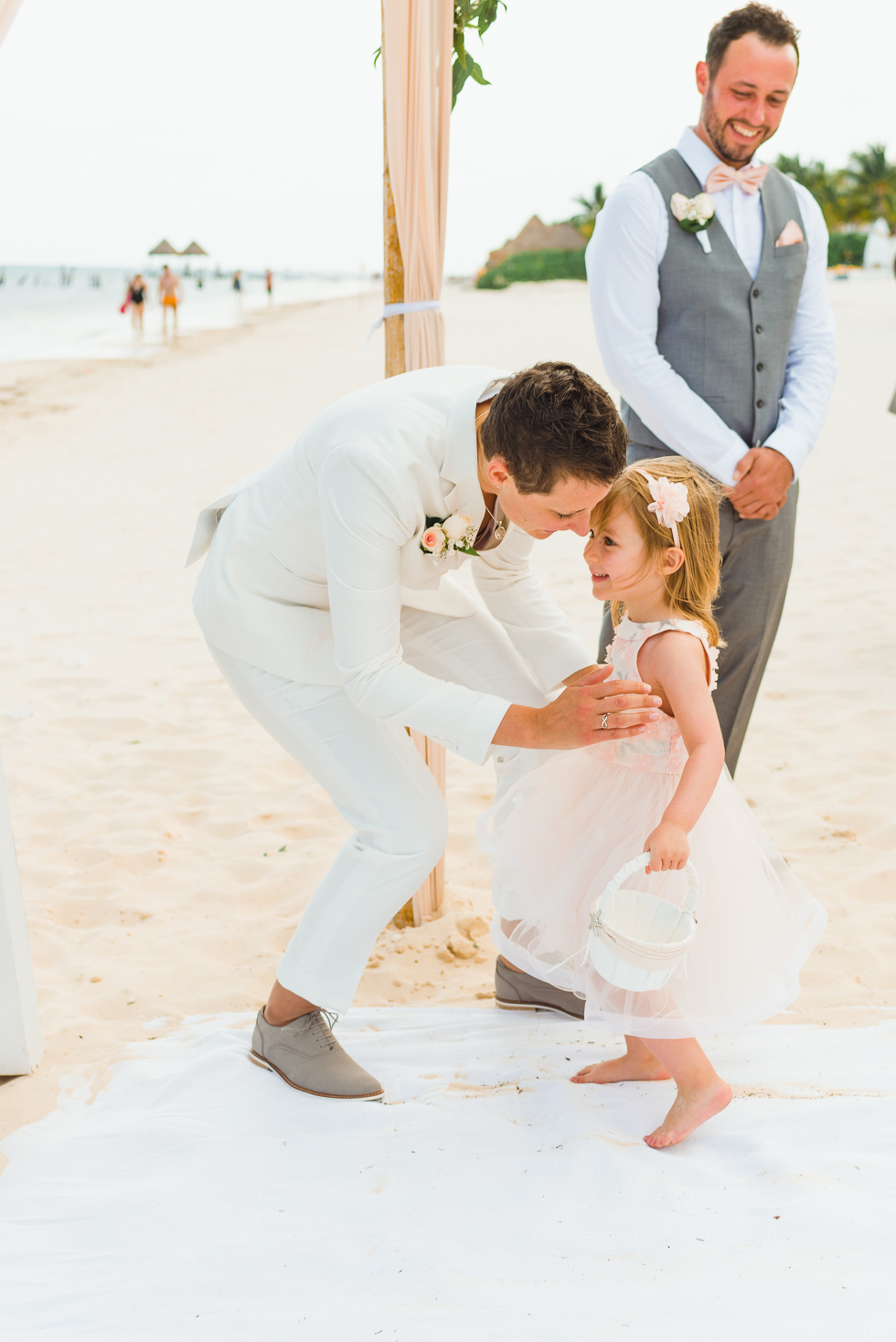 bride crouching down to greet a young girl at the wedding alter as a groomsman watches with a smile during beach ceremony at Now Sapphire Resort in Mexico