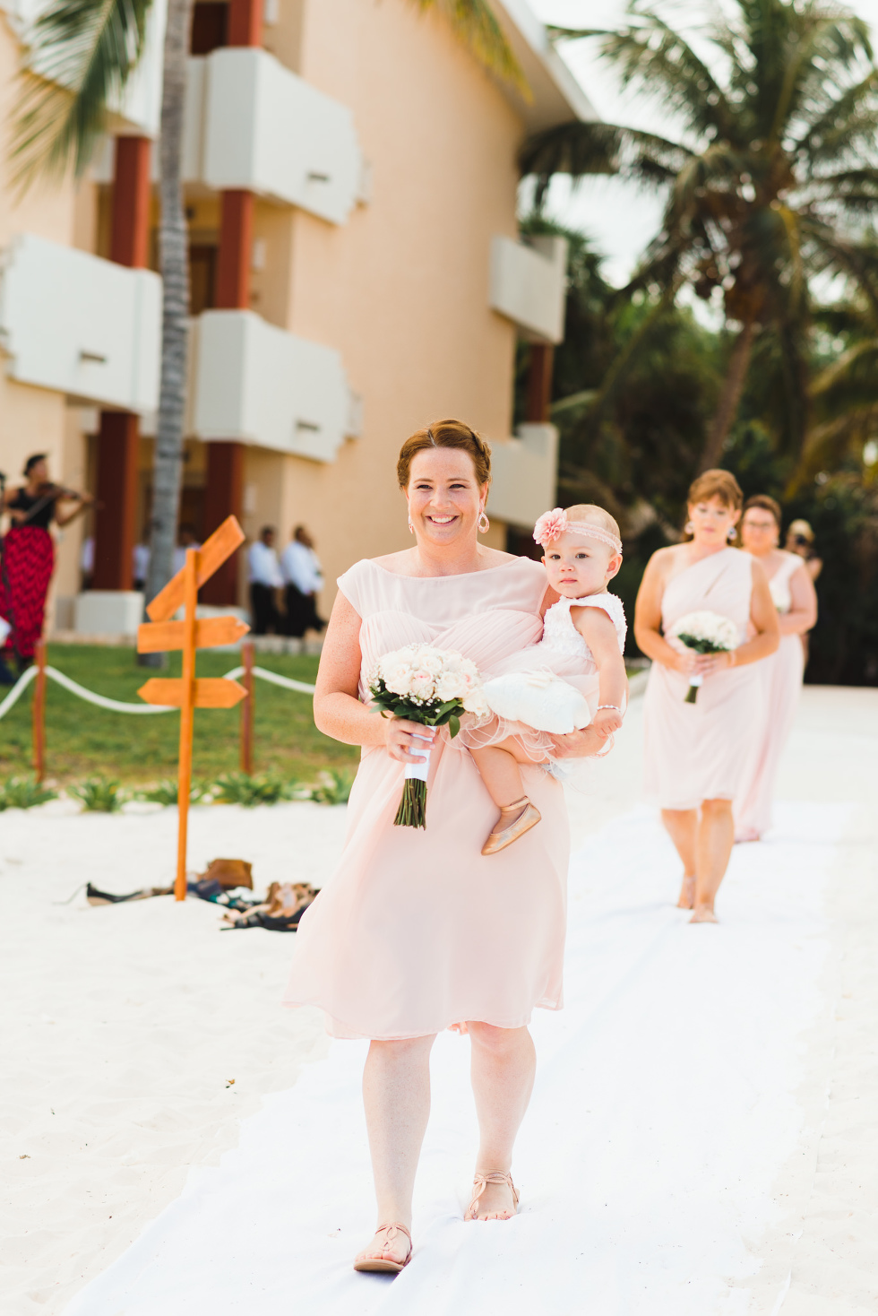 bridesmaid walking down aisle with her baby and a bouquet in her arms at beach wedding ceremony at Now Sapphire Resort in Mexico