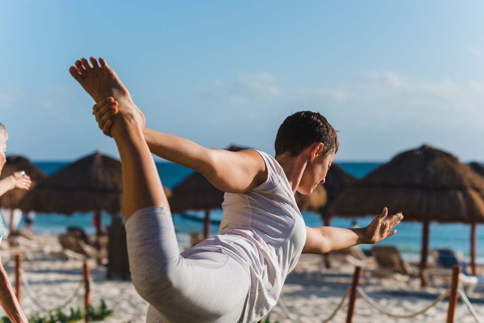 bride doing morning yoga on the beach at Now Sapphire Resort in Mexico