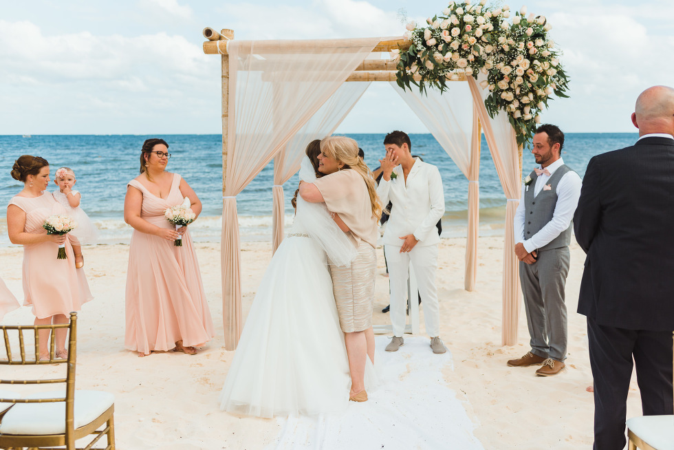 bride hugging mother at the wedding alter at a beach ceremony at Now Sapphire Resort in Mexico