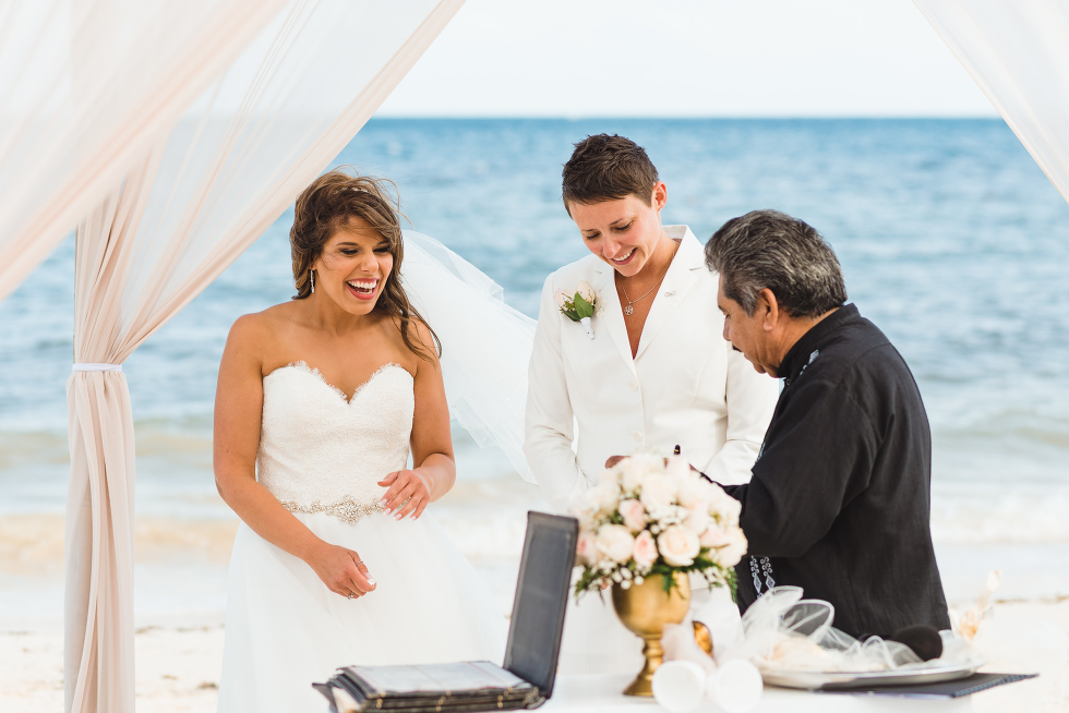 brides smiling at the alter as beach ceremony at Now Sapphire Resort in Mexico begins